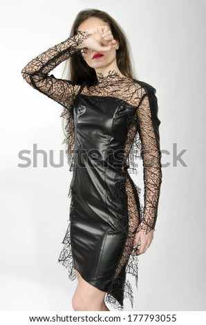 Beautiful brunette woman wearing a black leather dress and hiding her face with her hand - stock photo
