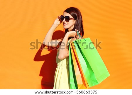 Beautiful brunette woman wearing a dress with shopping bags in city - stock photo