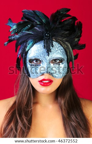 Beautiful brunette woman wearing a masqurade mask against a bright red background. - stock photo