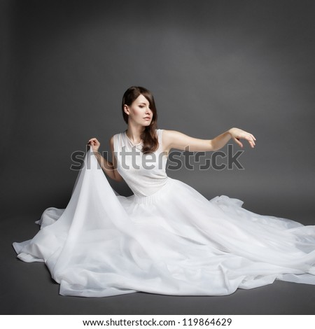 Beautiful brunette woman wearing elegant white dress. Fashion photo - stock photo
