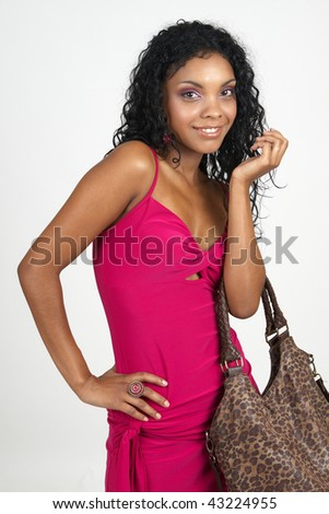 Beautiful brunette woman wearing pink cocktail dress and accessories smiling on white background. Not isolated