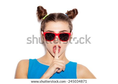 Beautiful brunette woman with a finger on her lips showing to keep silence, hush. Beauty girl with bright makeup hairstyle with horns in a blue dress having fun. White background, not isolated - stock photo