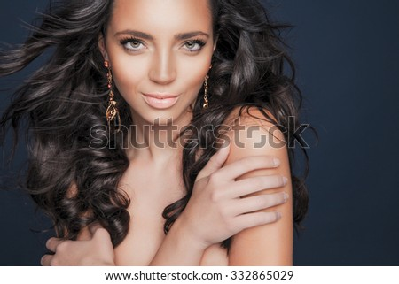 Beautiful brunette woman with beauty long curly hair and colorful makeup. Fashion model with wavy hairstyle. Toned in warm colors. Studio shot, horizontal - stock photo
