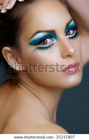Beautiful brunette woman with cat eyes make-up in turquoise and white, from 16bit RAW - stock photo