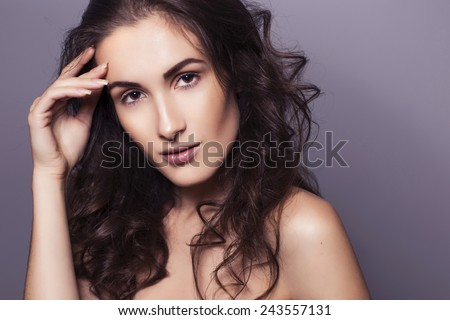Beautiful brunette woman with clear fresh skin and curly hair on a dark background, hand on face. toned image. copy space - stock photo