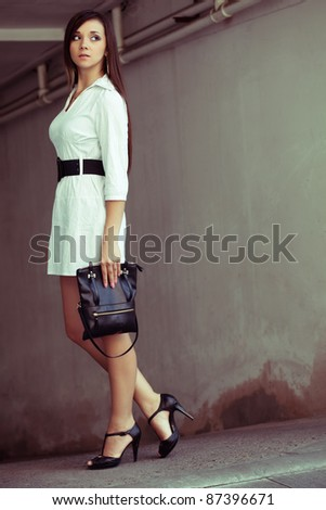 beautiful brunette woman with clutch looking around, outdoors fashion photo - stock photo