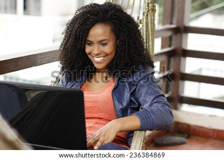 beautiful brunette woman with computer on the hammock