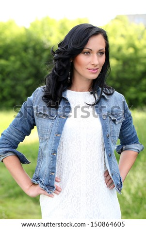 Beautiful brunette woman with curls and makeup in casual at the park