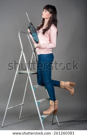 Beautiful brunette woman with heavy drill in her hands standing on ladder