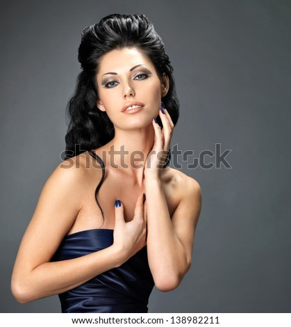 Beautiful brunette woman with long creative hairstyle.  Fashion model posing at studio  in the blue dress. - stock photo