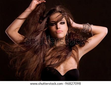 beautiful brunette woman with long flyng hair, studio dark - stock photo