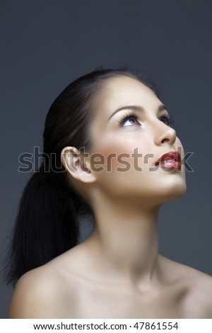 beautiful brunette woman with long hair and classic make-up looking up - stock photo