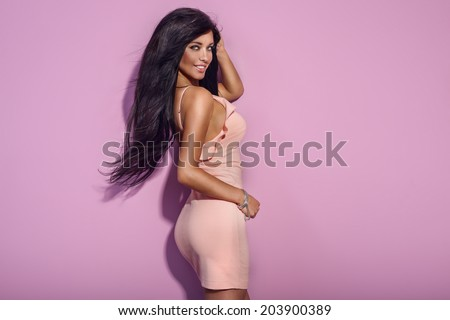 Beautiful brunette woman with long healthy brunette hair and amazing toothy smile looking at camera, posing in pink fashionable dress. - stock photo