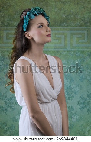 beautiful brunette woman with long wavy hair posing in spring portrait with white dress and flore on the head  - stock photo