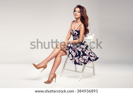 Beautiful brunette woman with lovely long hair posing in a sexy summer dress, sunglasses  in a studio. Fashion photo - stock photo