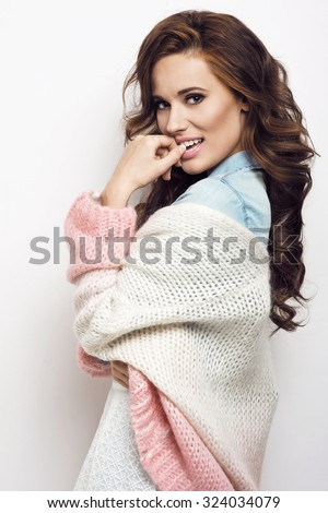 Beautiful brunette woman with lovely long hair posing in a sexy white sweater and jeans shirt in a studio. Fashion photo - stock photo
