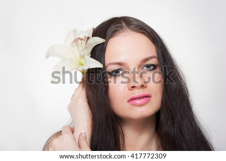 Beautiful brunette woman with orchid flower