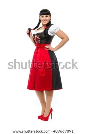 Beautiful brunette woman with pigtails in the Bavarian dressed smiling - stock photo