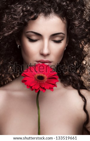 beautiful brunette woman with red flower - stock photo