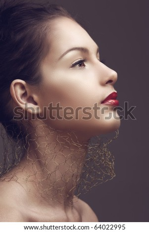 beautiful brunette woman with red lips and golden net around her neck in sepia cross-processed effect - stock photo