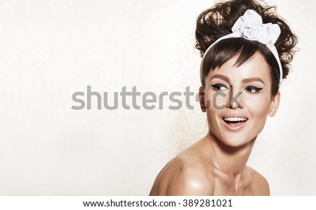 Beautiful brunette woman with retro hairdo and makeup. Luxury vogue style model posing in studio. Bridal makeup and wedding ideas concept. - stock photo