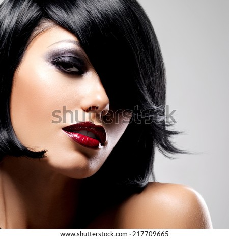 Beautiful brunette woman with shot hairstyle and sexy red lips. Closeup portrait of a female model with fashion makeup - stock photo