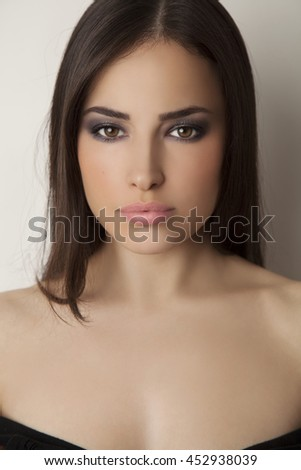 beautiful brunette woman with smokey eyes makeup, studio white