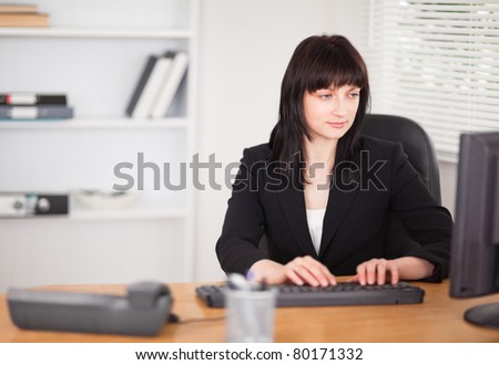 Beautiful brunette woman working on a computer while sitting at a desk in the office - stock photo