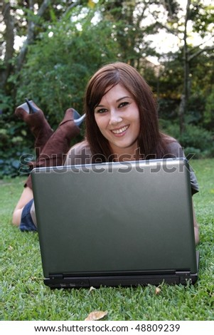 Beautiful brunette woman working on her laptop outdoors on green grass