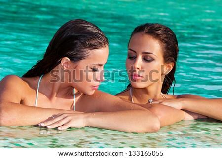 beautiful brunette women relax in pool - stock photo