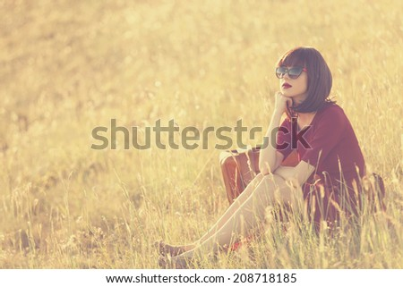 Beautiful brunette women with suitcase on autumn meadow in sunset time - stock photo