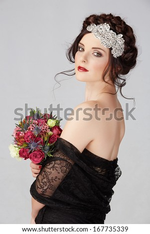 Beautiful brunette young bride with braided hair with shiny crown wearing black lace dress in studio - stock photo