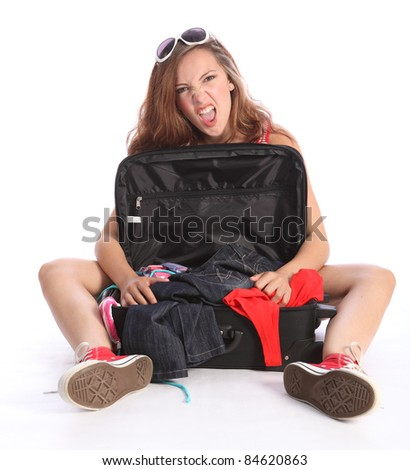 Beautiful brunette young teenager school girl sitting on floor with suitcase having fun packing for her holiday. Case is open showing clothes untidy inside. - stock photo