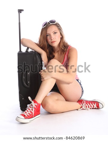Beautiful brunette young teenager school girl with long hair and sunglasses, sitting on floor with suitcase packed and ready to travel but looking fed up and tired. - stock photo