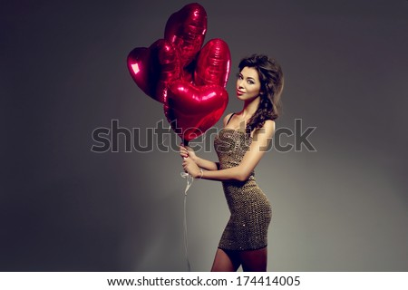 Beautiful brunette young woman in golden dress with a heart-shaped balloons. Valentine's day - stock photo