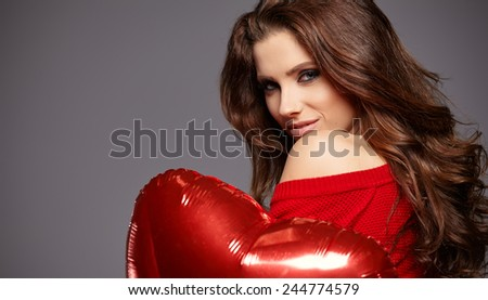 Beautiful brunette young woman in red with a heart-shaped balloons  - stock photo