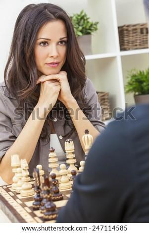 Beautiful brunette young woman playing chess game with man, boyfriend, husband  - stock photo