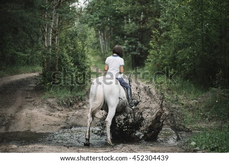 Beautiful brunette young woman riding her white horse in the summer forest. White horse happily jumps on the mud paddock - stock photo