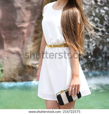 Beautiful brunette young woman wearing white romantic dress with little handbag and walking outdoor - stock photo