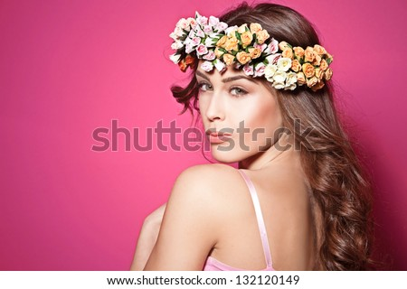beautiful brunette young woman with wreath of flowers studio shot pink background - stock photo