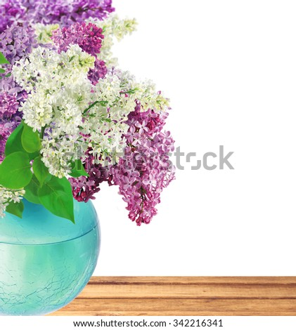 Beautiful Bunch of Lilac in the Vase on wooden table over white