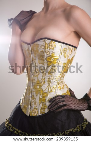 Beautiful burlesque girl in golden corset and black skirt, studio shot  - stock photo