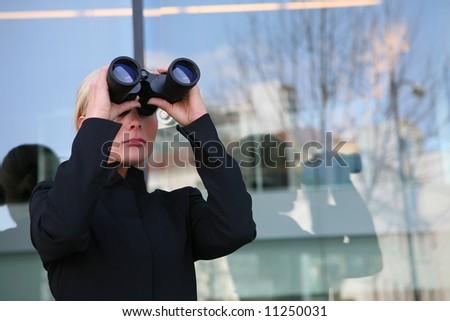 Beautiful business blonde woman looking through binoculars - stock photo