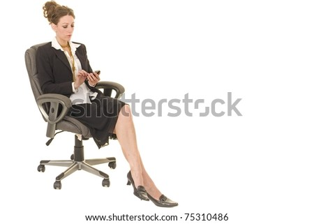 Beautiful business executive sits on chair and uses phone