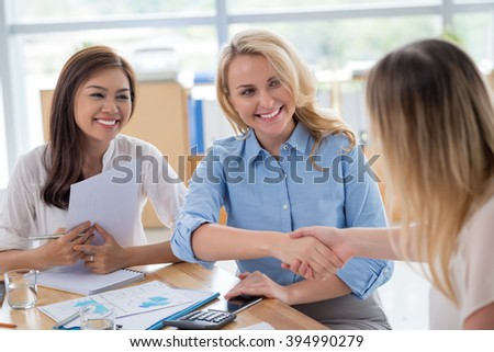 Beautiful business ladies shaking hands at the meeting
