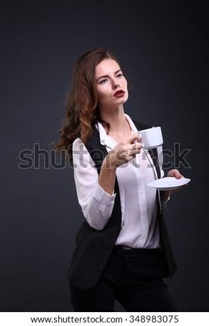 Beautiful business lady holding white cup of coffee  on a dark background. Studio shot