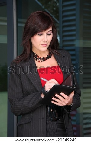 Beautiful business lady writing in her book