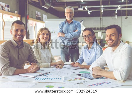 Beautiful business people in classic shirts are looking at camera and smiling while working in office