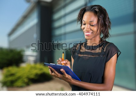 Beautiful business professional, african woman making notes - stock photo