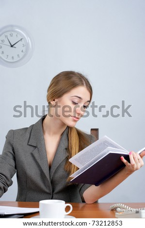 Beautiful business woman at desk, reading book - stock photo